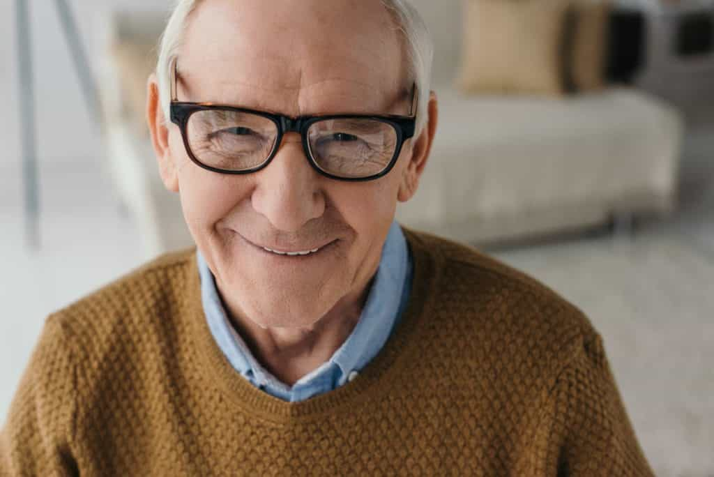 elderly man with glasses smiling